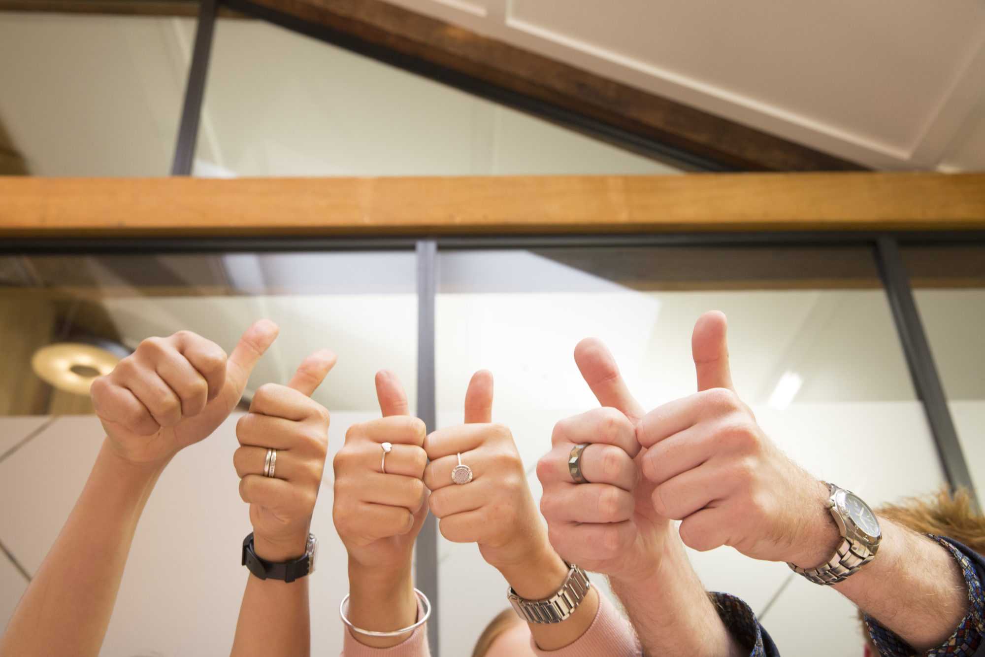 Employees in workplace with thumbs up demonstrating workplace wellness