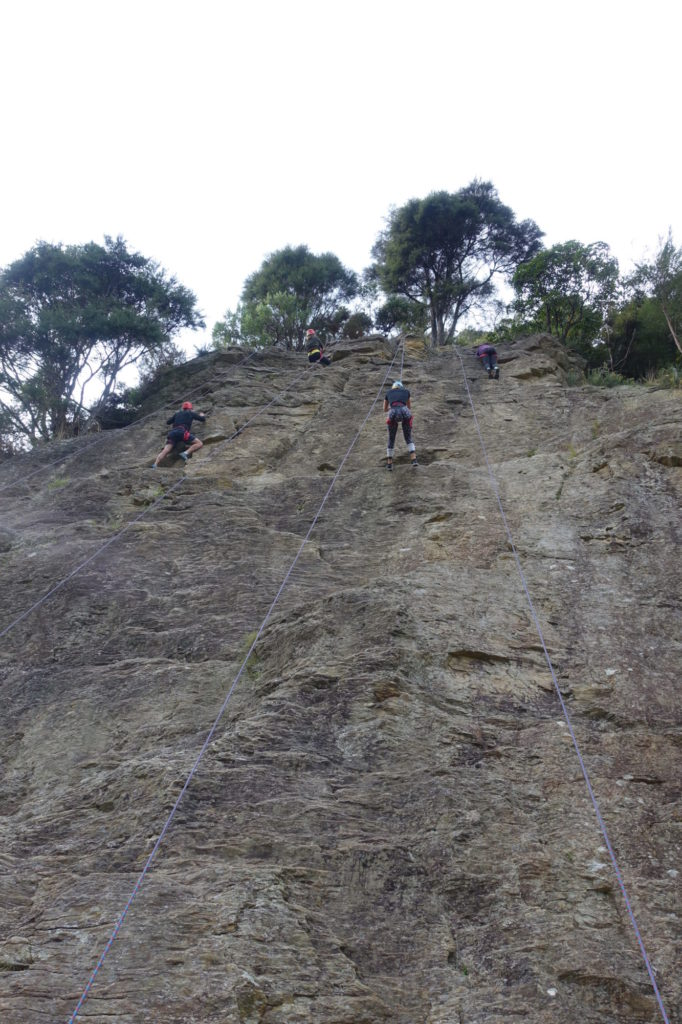 Rock wall climbing with four climbers at Outward Bound, Anakiwa, NZ