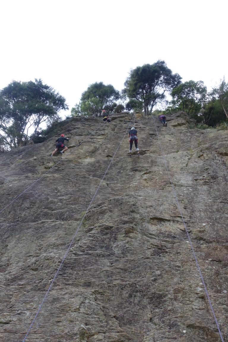 Rock wall climbing with four climbers at Outward Bound, Anakiwa, NZ